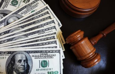 An image of several $100 bills laid out next to a gavel, representing court money.