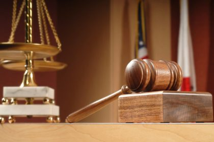 An image courtroom items - a gavel, the United States of America flag, and decorative Scales of Justice.