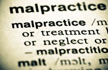 Image of a dictionary definition of malpractice, with the word malpractice showing, while all other words are blurred except
